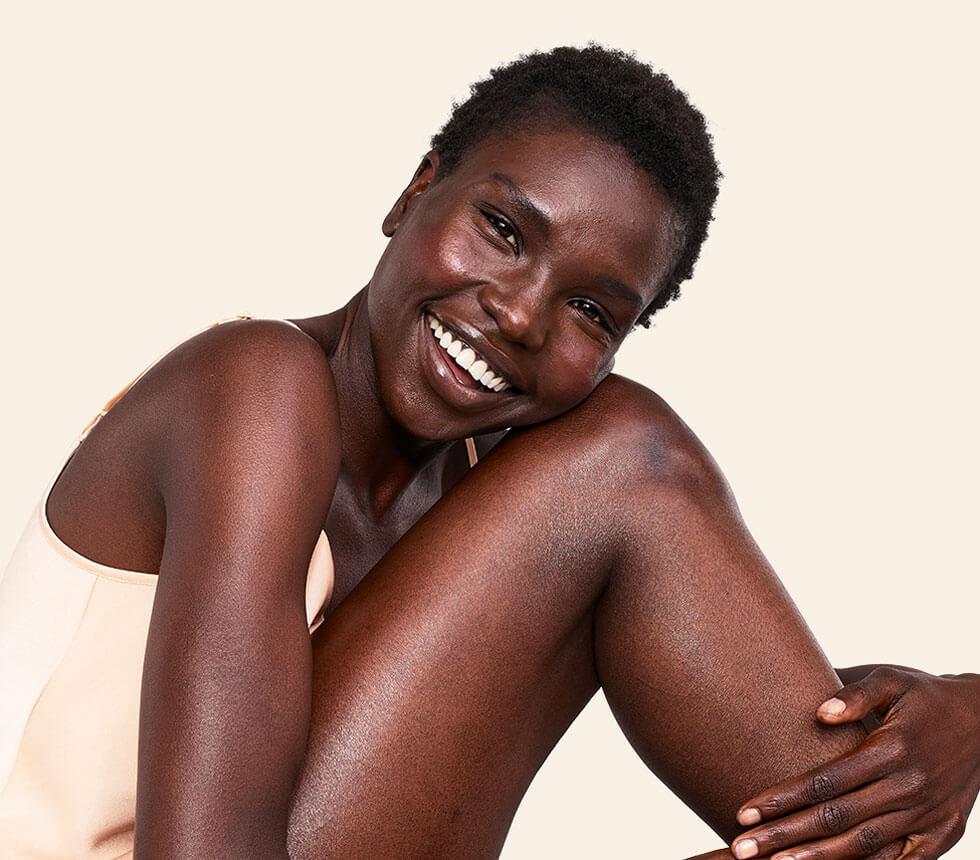 una donna sorridente con la pelle di viso e corpo luminosa grazie ad aveeno